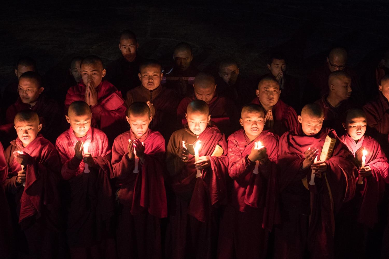 Novice monks praying to candlelight