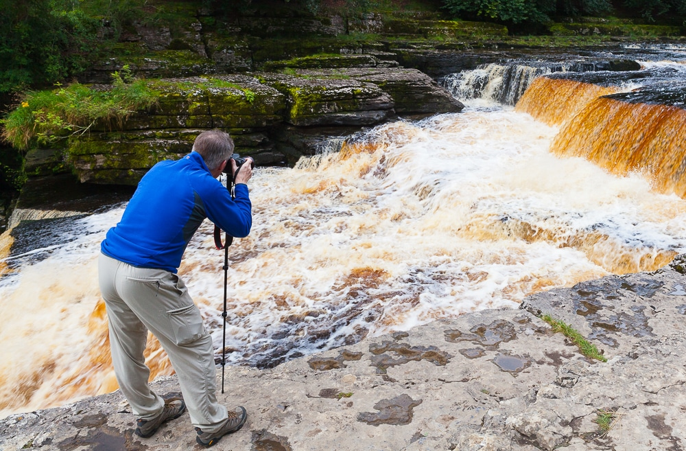 photographer photographing waterfall