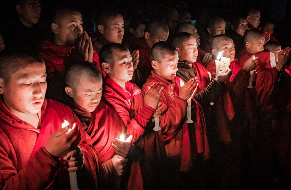 Monks during evening candle light prayer in Lhodrak Kharchu monastery, Jakar, Bumthang District, Bhutan