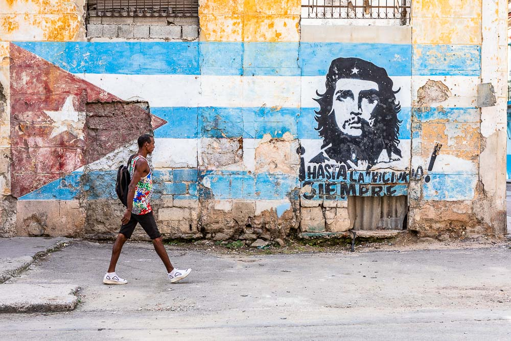 A man walking in a front of Che Guevara street art in La Habana Vieja (Old Town), Havana, Cuba